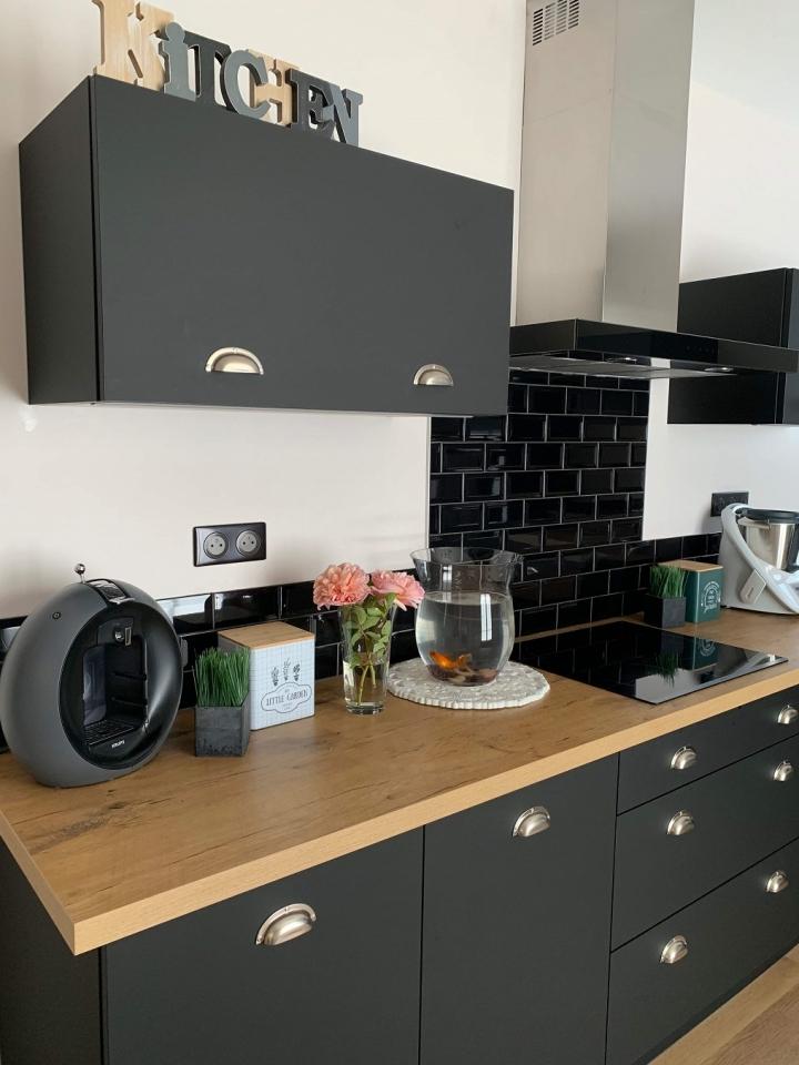 Cuisine coloris noir extra-mat avec des poignées coquille et un plan de travail décor bois